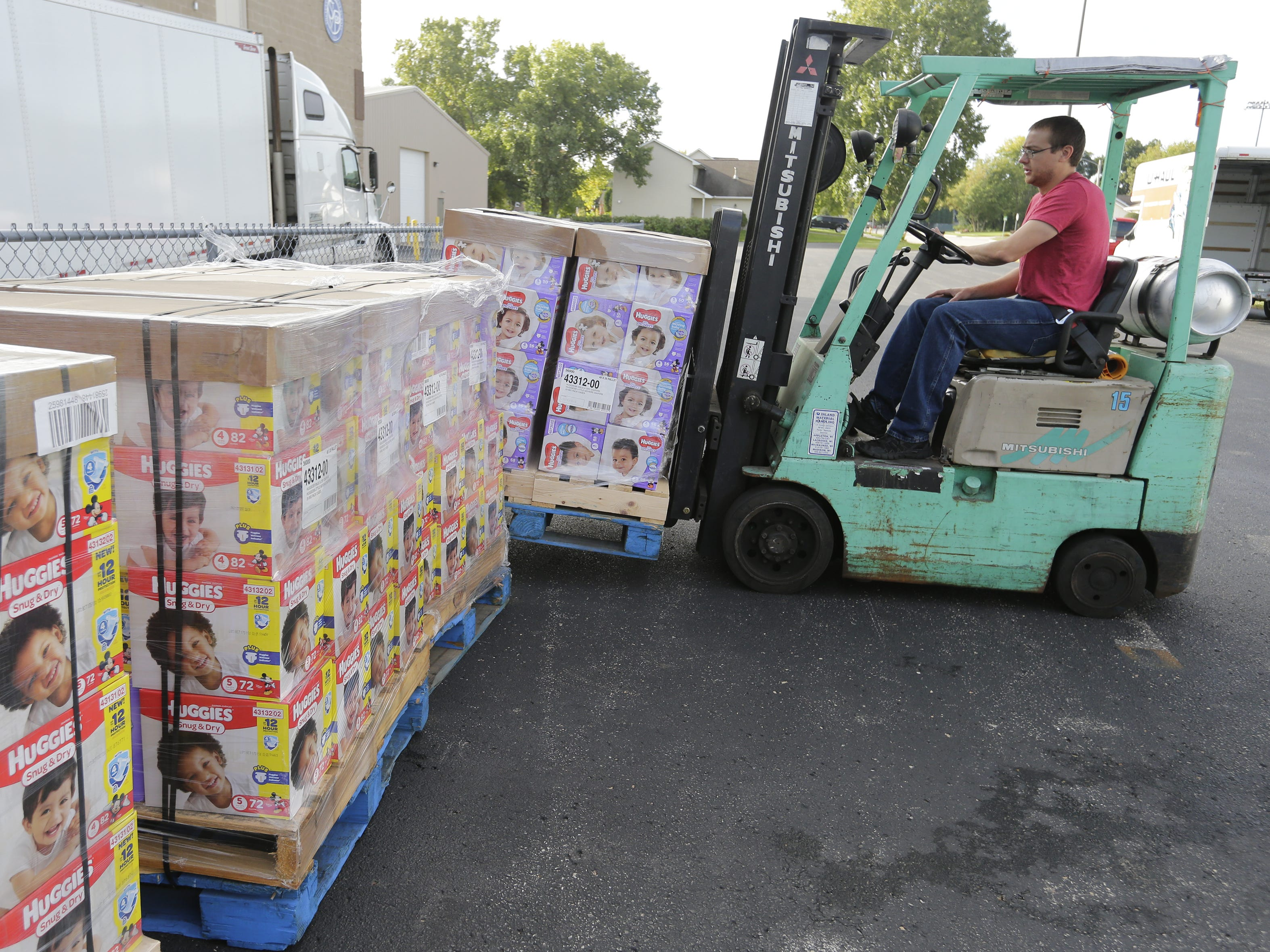 Brandon Wittman of the Oshkosh Area Community Food Pantry positions pallets of diapers for distribution Monday, Sept. 24, 2018, in Oshkosh. USA TODAY NETWORK-Wisconsin and Kimberly-Clark Corp. donated 100,400 diapers to nine food pantries in the area.