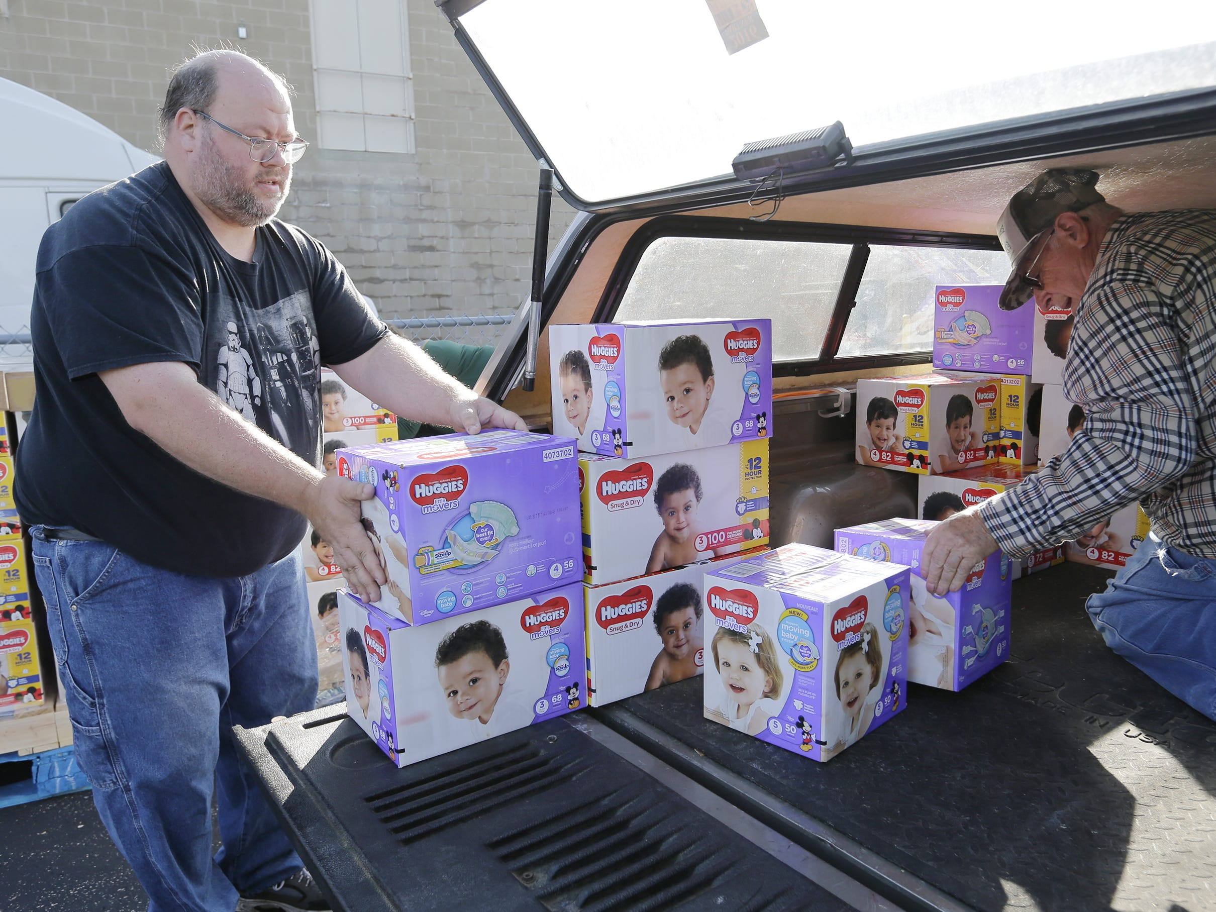 Chris Boelter, a volunteer with the Oshkosh Area Community Food Pantry, helps Bill Joch of the Omro Community Food Pantry load his vehicle with the diapers Monday, Sept. 24, 2018, in Oshkosh. USA TODAY NETWORK-Wisconsin and Kimberly-Clark Corp. donated 100,400 diapers to nine food pantries in the area.