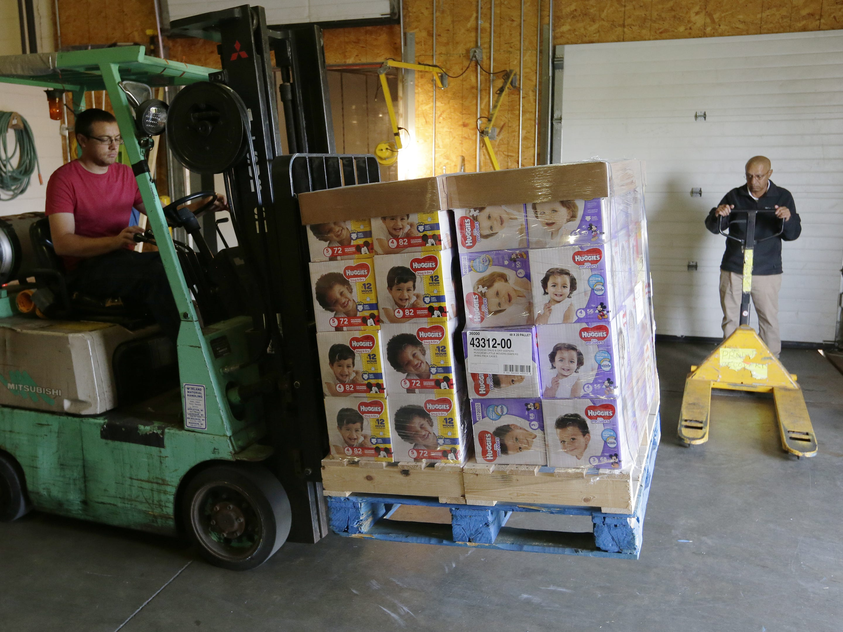 Brandon Wittman of the Oshkosh Area Community Food Pantry unloads diapers as Hussian Sattar of Father Carr's Place 2B waits to take them outside for distribution Monday, Sept. 24, 2018, in Oshkosh. USA TODAY NETWORK-Wisconsin and Kimberly-Clark Corp. donated 100,400 diapers to nine food pantries in the area.