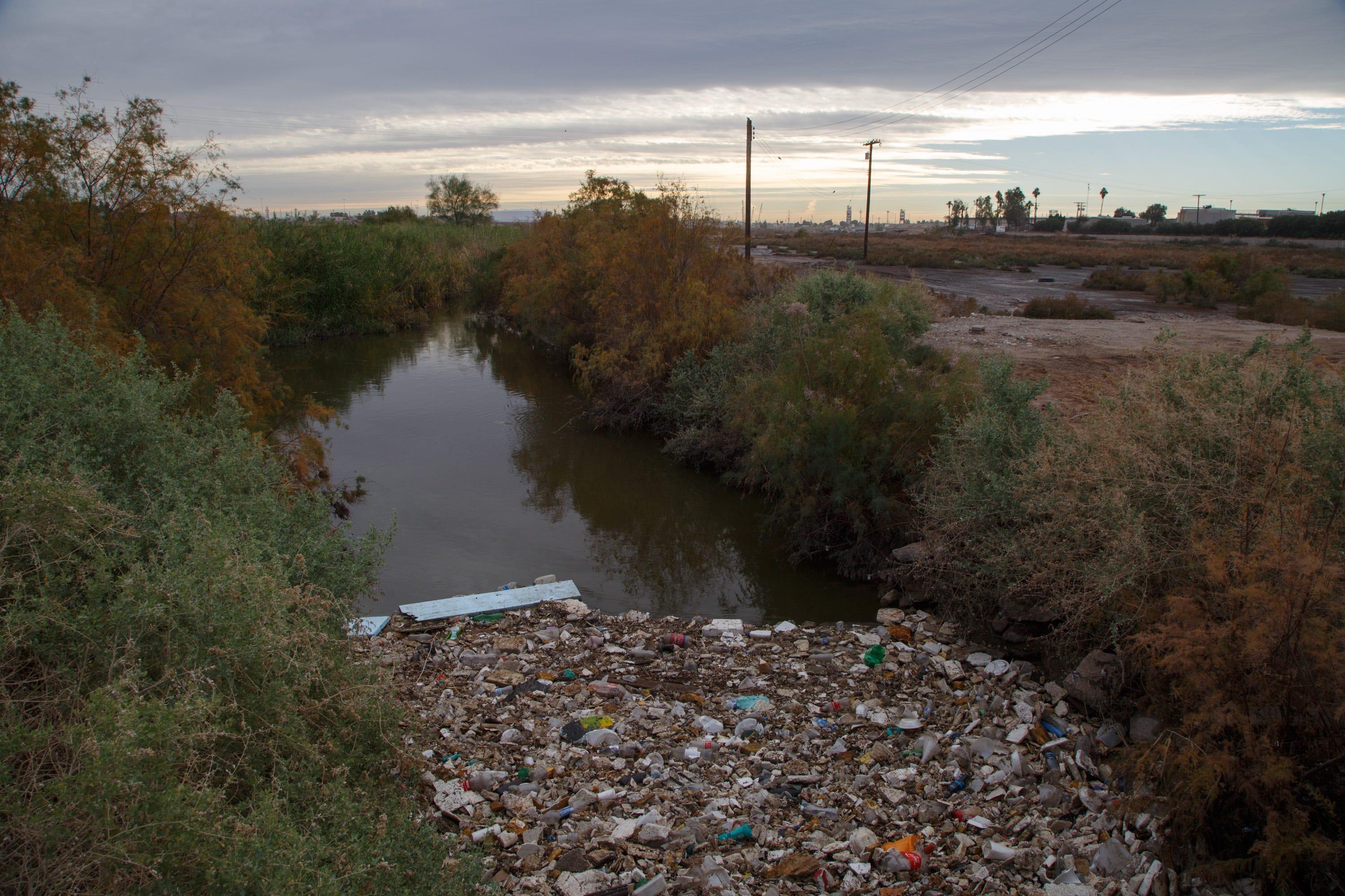 Floating trash collects in the New River near the border in Calexico.