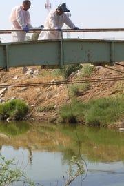 Empleados de la Junta Regional de Control de Calidad del Agua de California toman una muestra de agua del New River en Calexico.