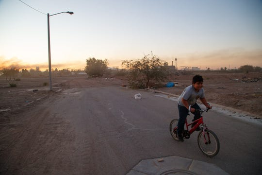 A boy rides a bicycle in a neighborhood next to a factory in Mexicali.