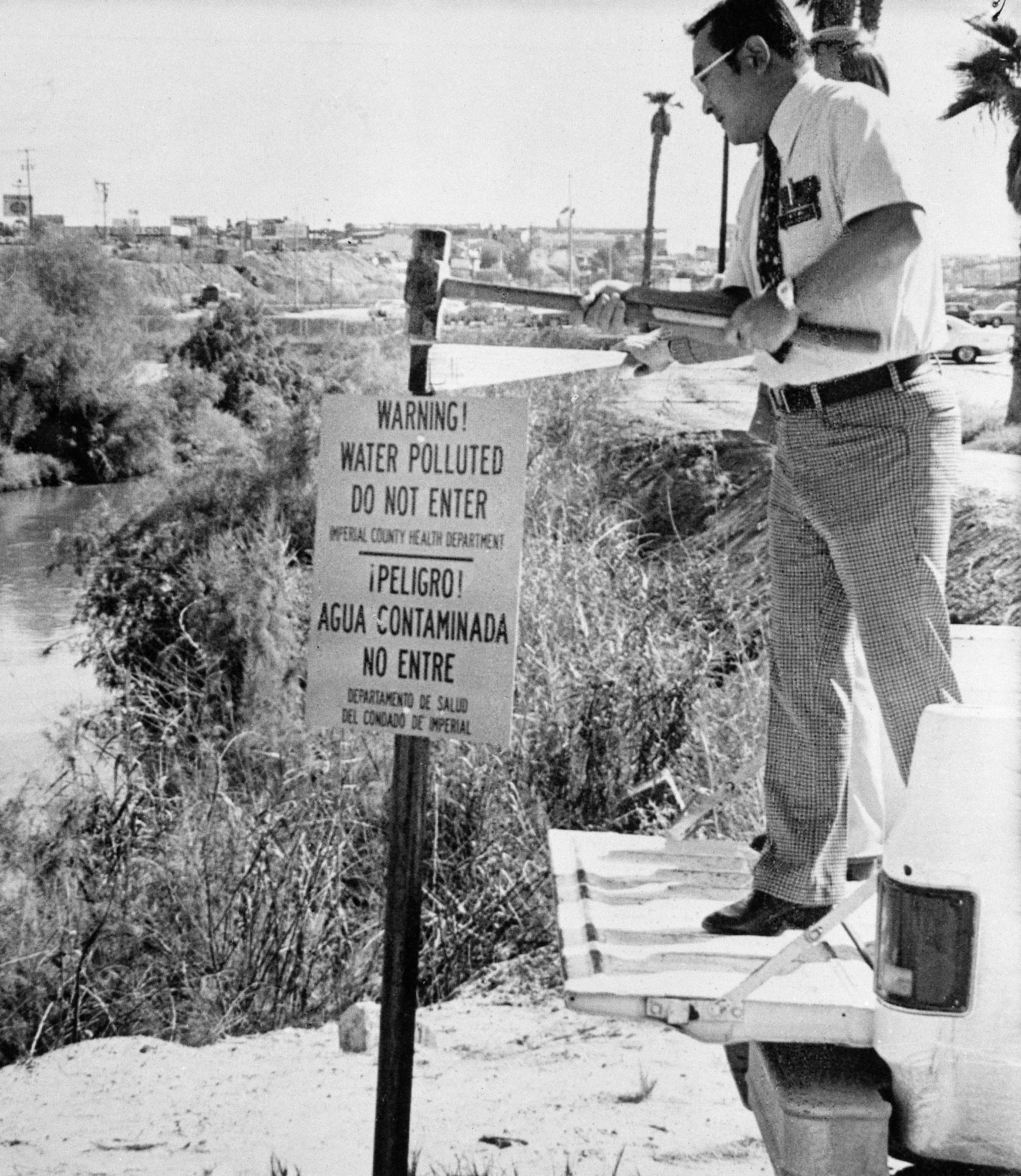 Dr. William Hsu, Imperial County's director of environmental health, erects a sign warning people to stay out of the dangerously polluted New River in Calexico on Nov. 14, 1978.