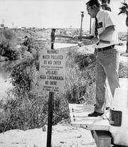 El Dr. William Hsu, director de salud ambiental del Condado Imperial, erige un letrero que advierte a las personas que deben mantenerse fuera del peligroso New River en Calexico, el 14 de noviembre de 1978