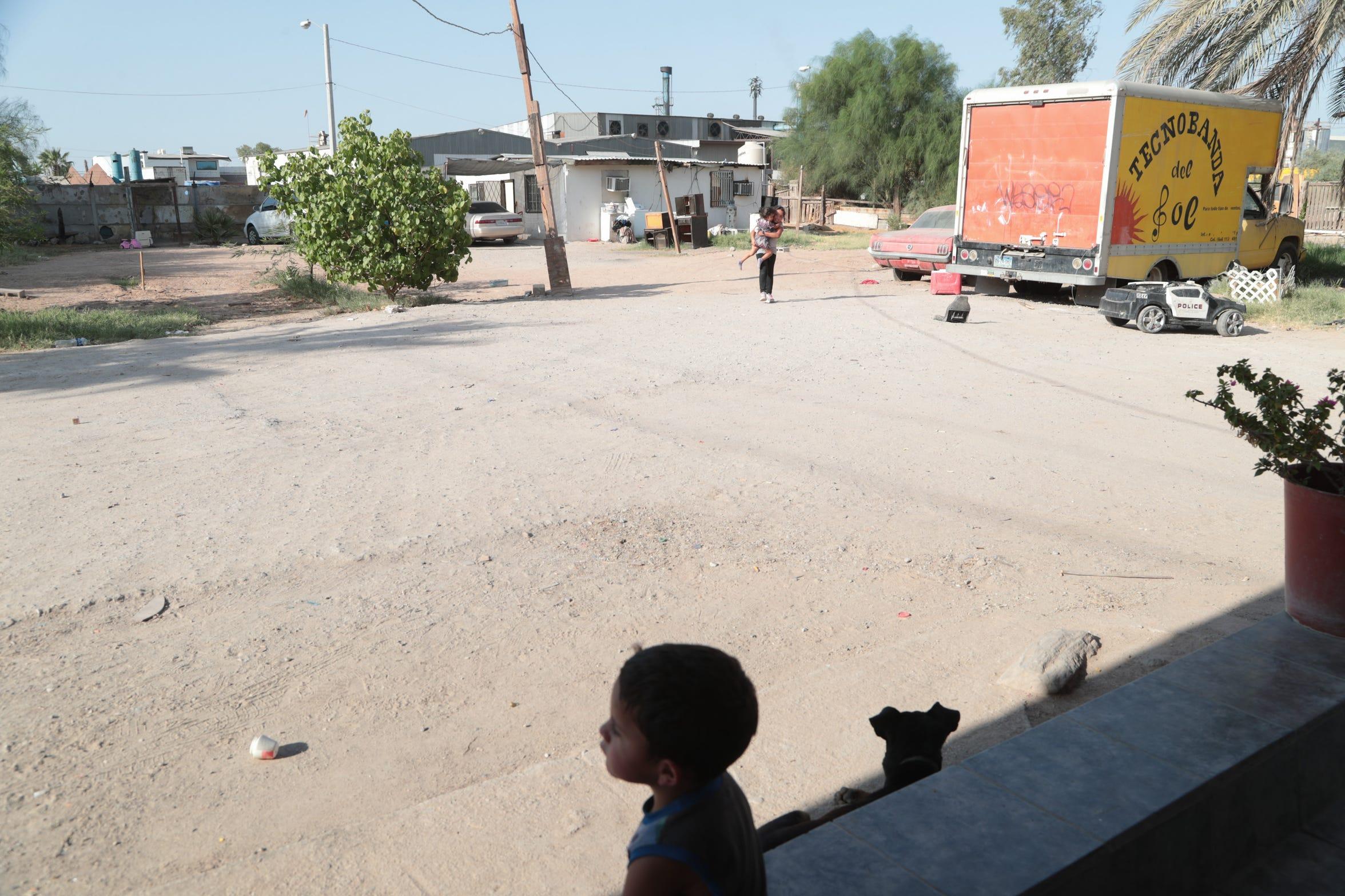 Niños juegan afuera de su casa ubicada cerca de la fábrica Industrias Zahori en Mexicali.