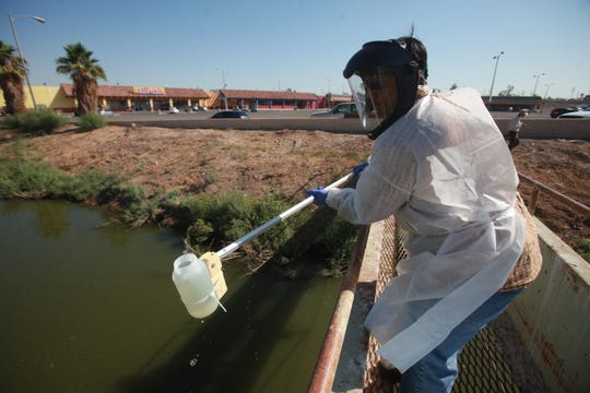 An employee of the California Regional Water Quality Control Board takes a water sample from the New River in Calexico, Ca.
