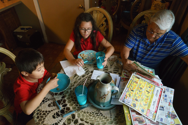 Ciro Calderón sits with his grandchildren at his home in Calexico.