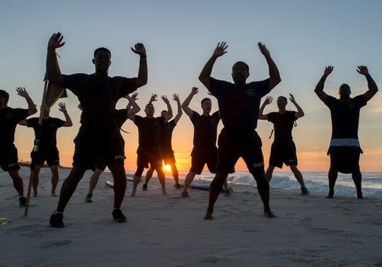 Chief petty officer selectees do calisthenics Sept. 12 as the sun rises during an early morning physical training session at Gulf Islands National Seashore in Perdido Key.