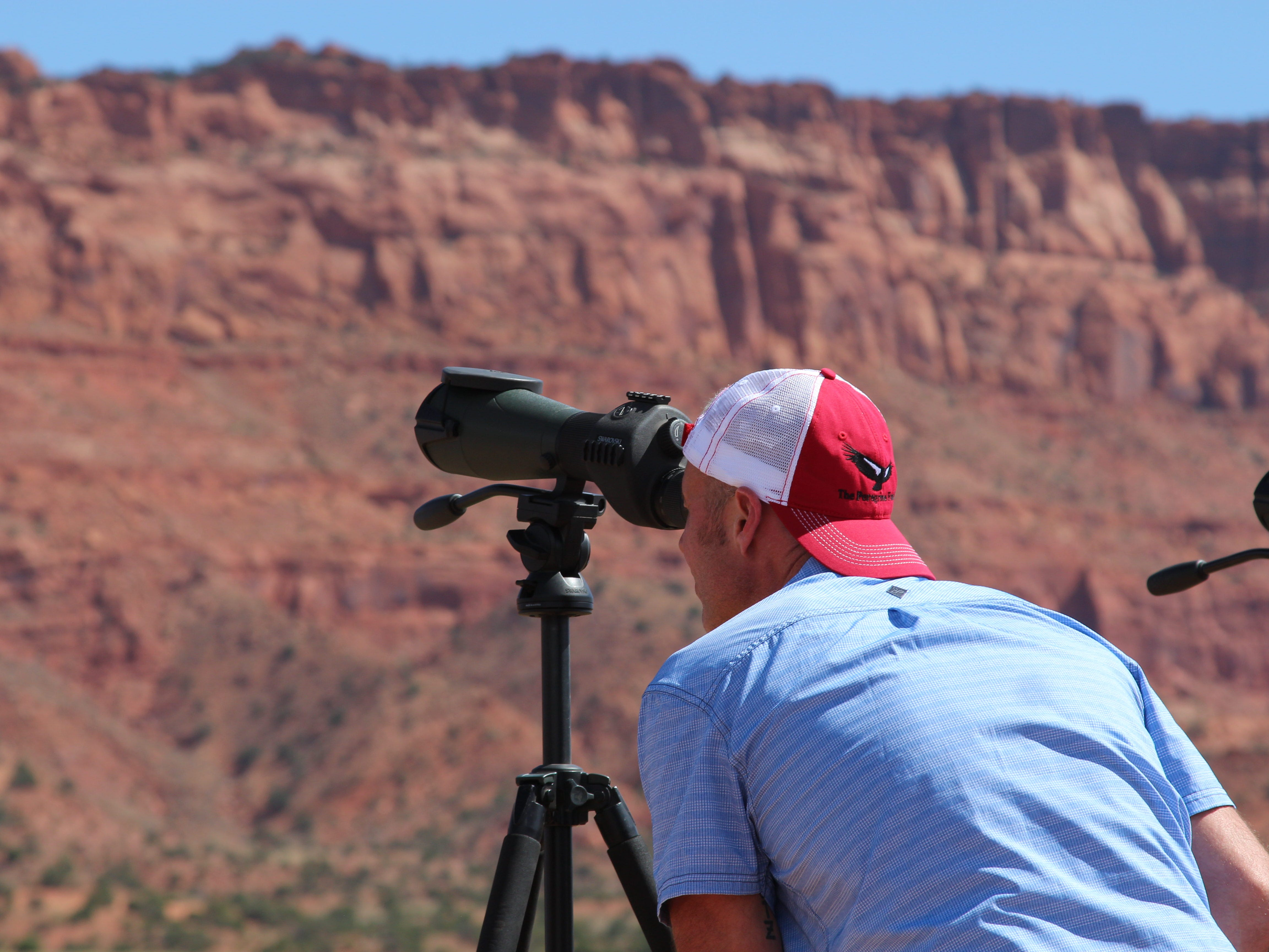 A visitor to Vermilion Cliffs National Monument peers through a viewing scope to look for California condors, newly released  into the wild on Sept. 22, 2018.