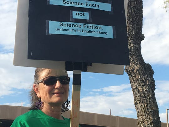 A woman protests changes to Arizona's science standards on Sept. 24 before a State Board of Education meeting.