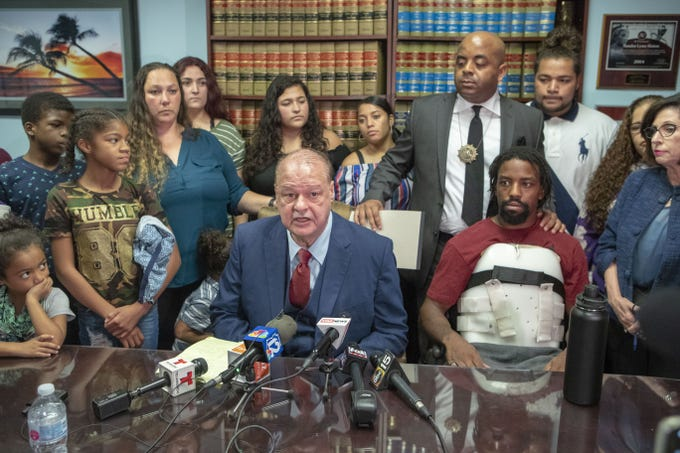 Former AG Tom Horne (center) and speaks at a press conference for Horne's client Edward Brown (right), who is paralyzed from the chest down since being shot by a Phoenix police officer in August.