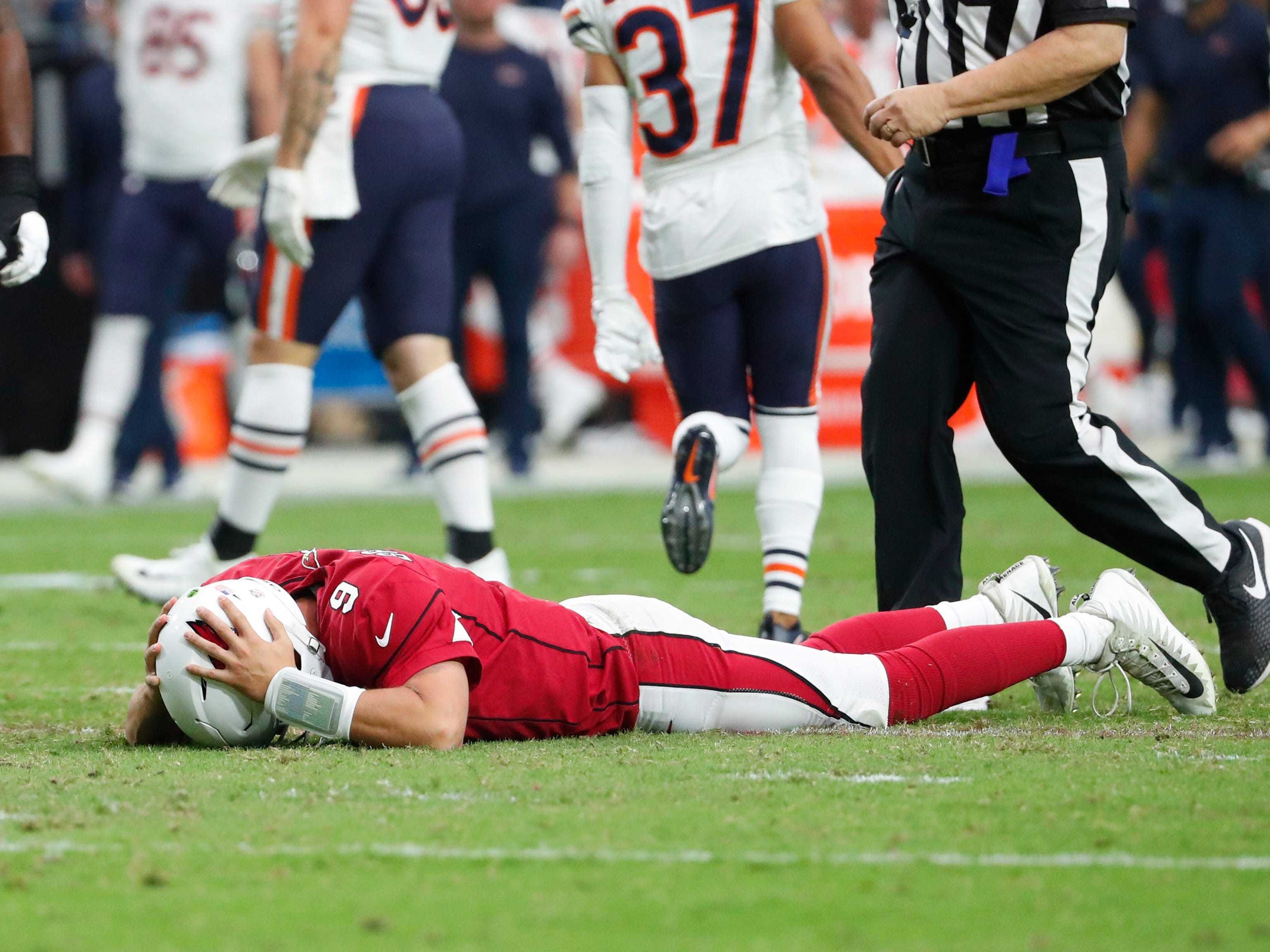 Arizona Cardinals quarterback Sam Bradford (9) lays on the ground after fumbling the ball to the Chicago Bears during the fourth quarter at State Farm Stadium in Glendale, Ariz. September 23, 2018.