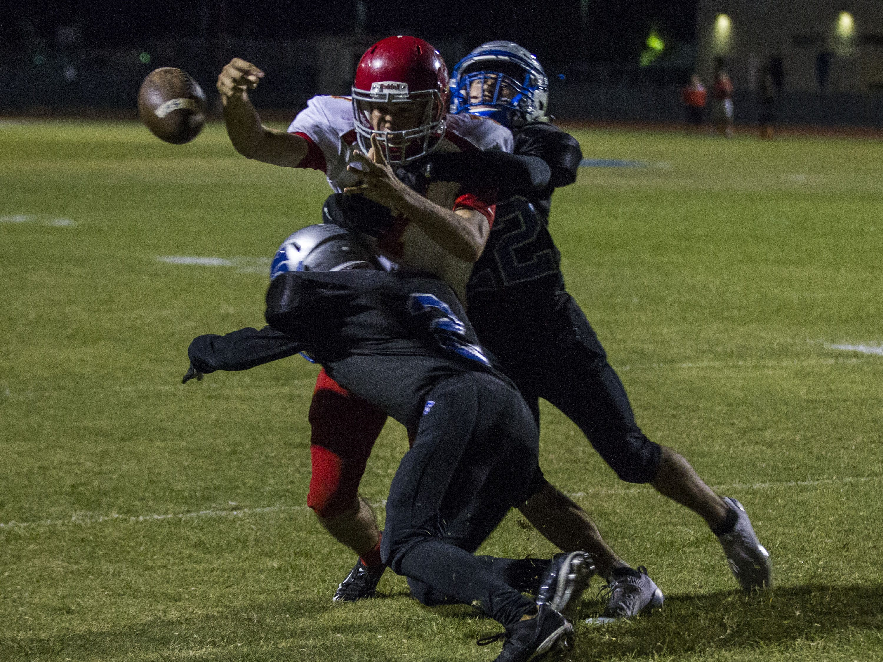 Seton quarterback Vincent Wallace loses the ball after getting sandwiched by Mesquite's Ramon Corella(2) and Chris Hintze (22) during their game in Gilbert Friday, Sept. 21, 2018. #azhsfb