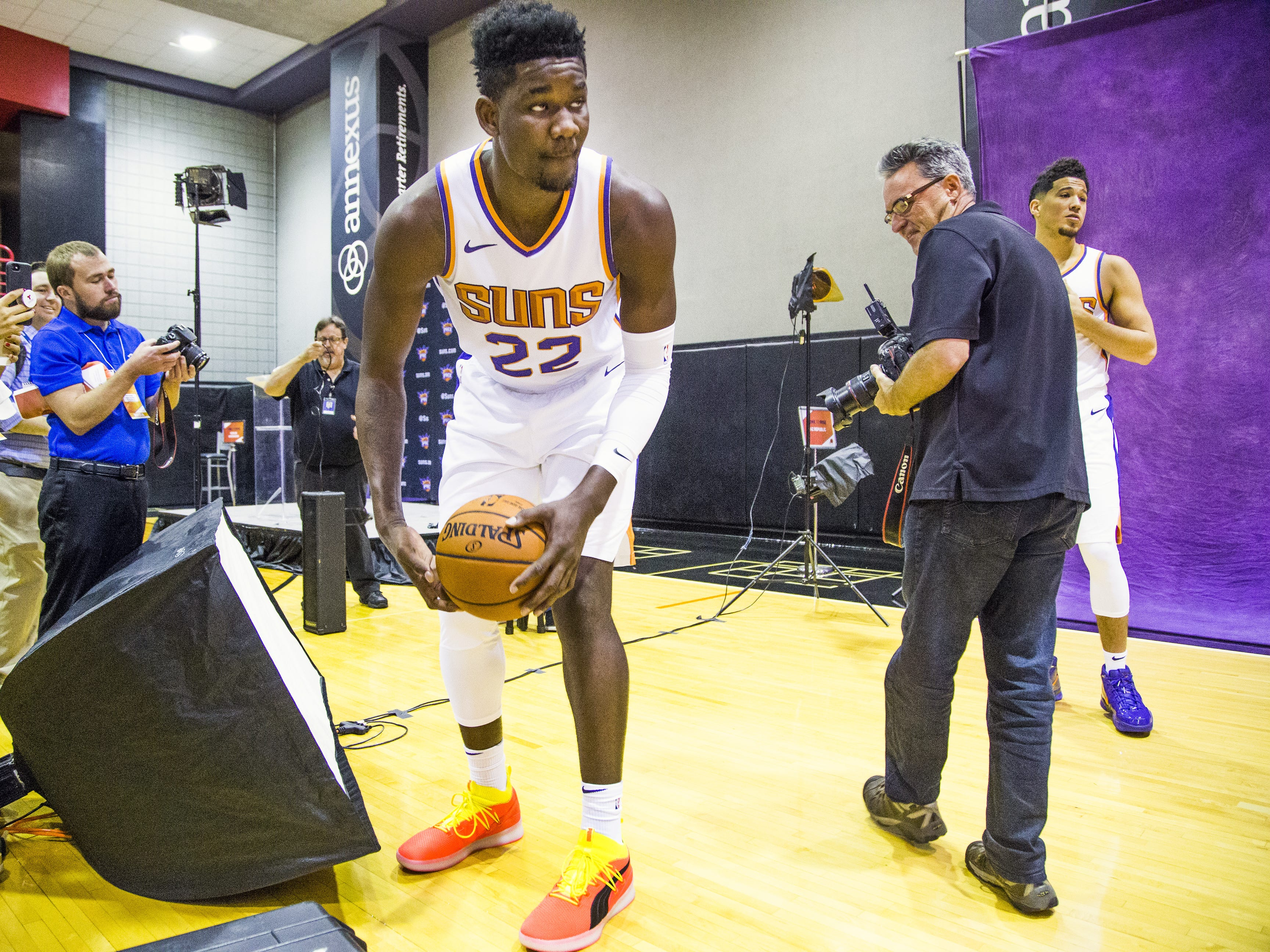 Deandre Ayton, center for the Phoenix Suns, picks up a basketball as Arizona Republic photographer Rob Schumacher prepares to photograph Ayton and Phoenix Suns guard Devin Booker, right, at Phoenix Suns Media Day at Talking Stick Resort Arena in Phoenix, Monday, September 24, 2018.