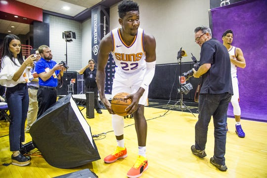 Deandre Ayton picks up a basketball as Arizona Republic photographer Rob Schumacher prepares to photograph Ayton and Devin Booker, right, at Phoenix Suns media day on Sept. 24.