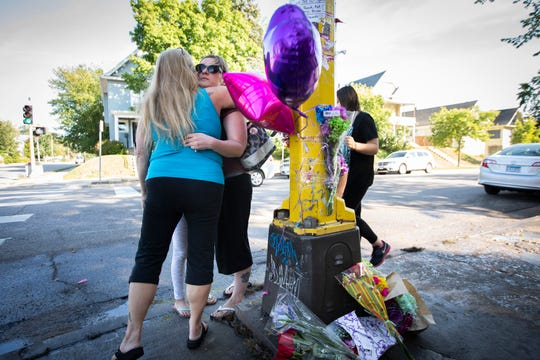 People who identified only as extended members of the family of Sheryl and Kenneth Carpentier, two of the victims, hug after putting up balloons and flowers on a memorial for the victims in Minneapolis on Sunday, Sept. 23, 2018.