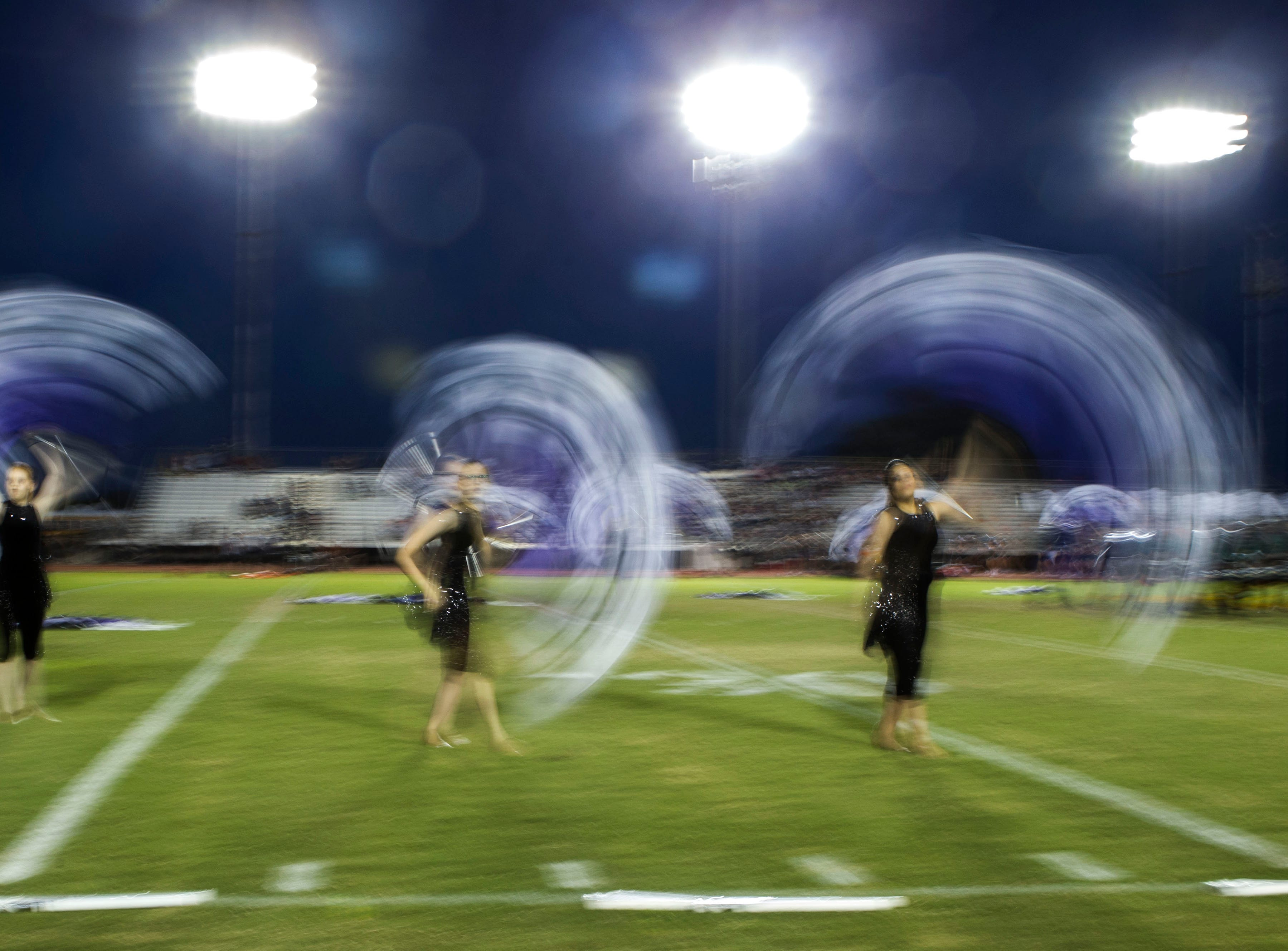 The Gilbert Campo Verde drill team twirls flags before a game at Gilbert High on Friday, Sept. 21, 2018. #azhsfb