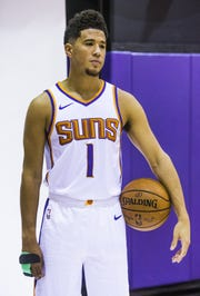 Devin Booker poses with a splint on his right hand at Suns media day on Monday.