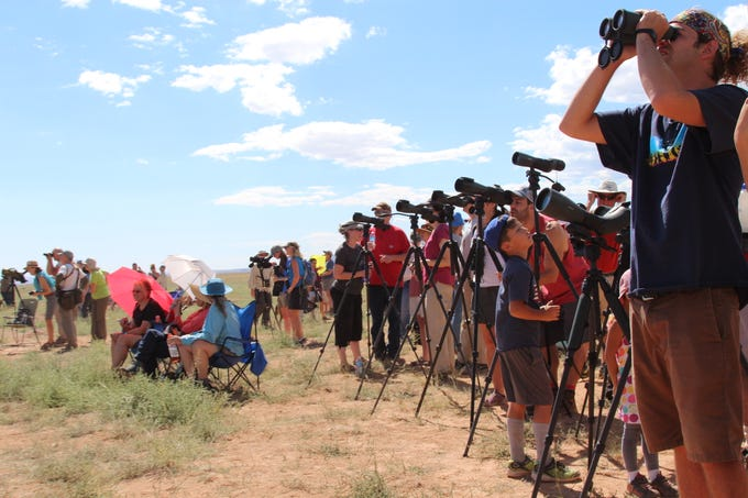 Visitors to Vermilion Cliffs National Monument peer through viewing scopes and binoculars to look for California condors, newly released  into the wild on Sept. 22, 2018.