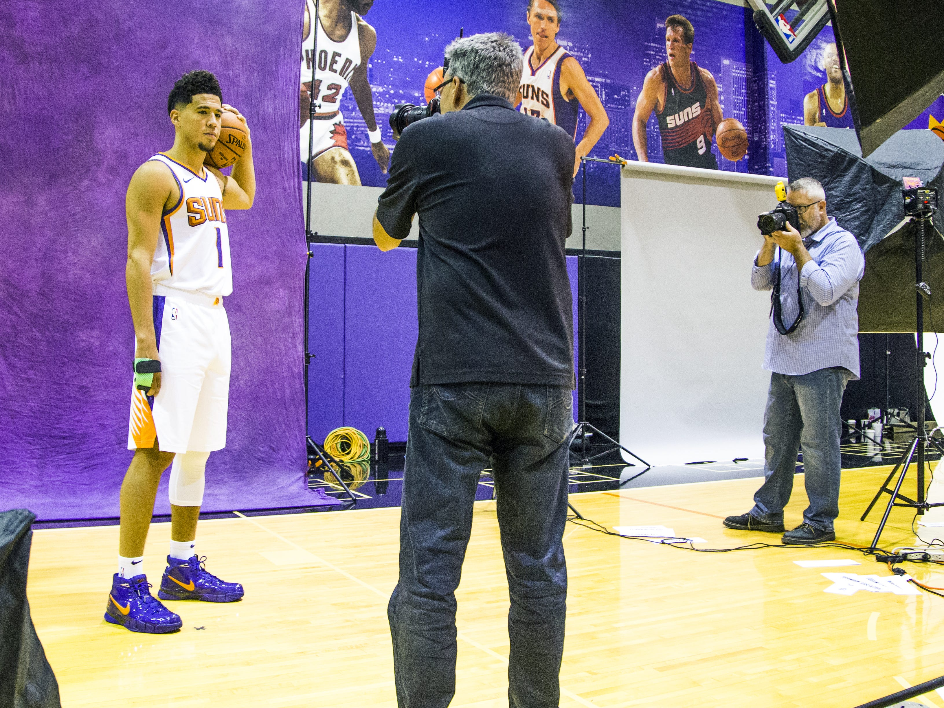 Arizona Republic photographer Rob Schumacher, left, and Associated Press photographer Matt York, right, take photos of Phoenix Suns guard Devin Booker at Phoenix Suns Media Day at Talking Stick Resort Arena in Phoenix, Monday, September 24, 2018.