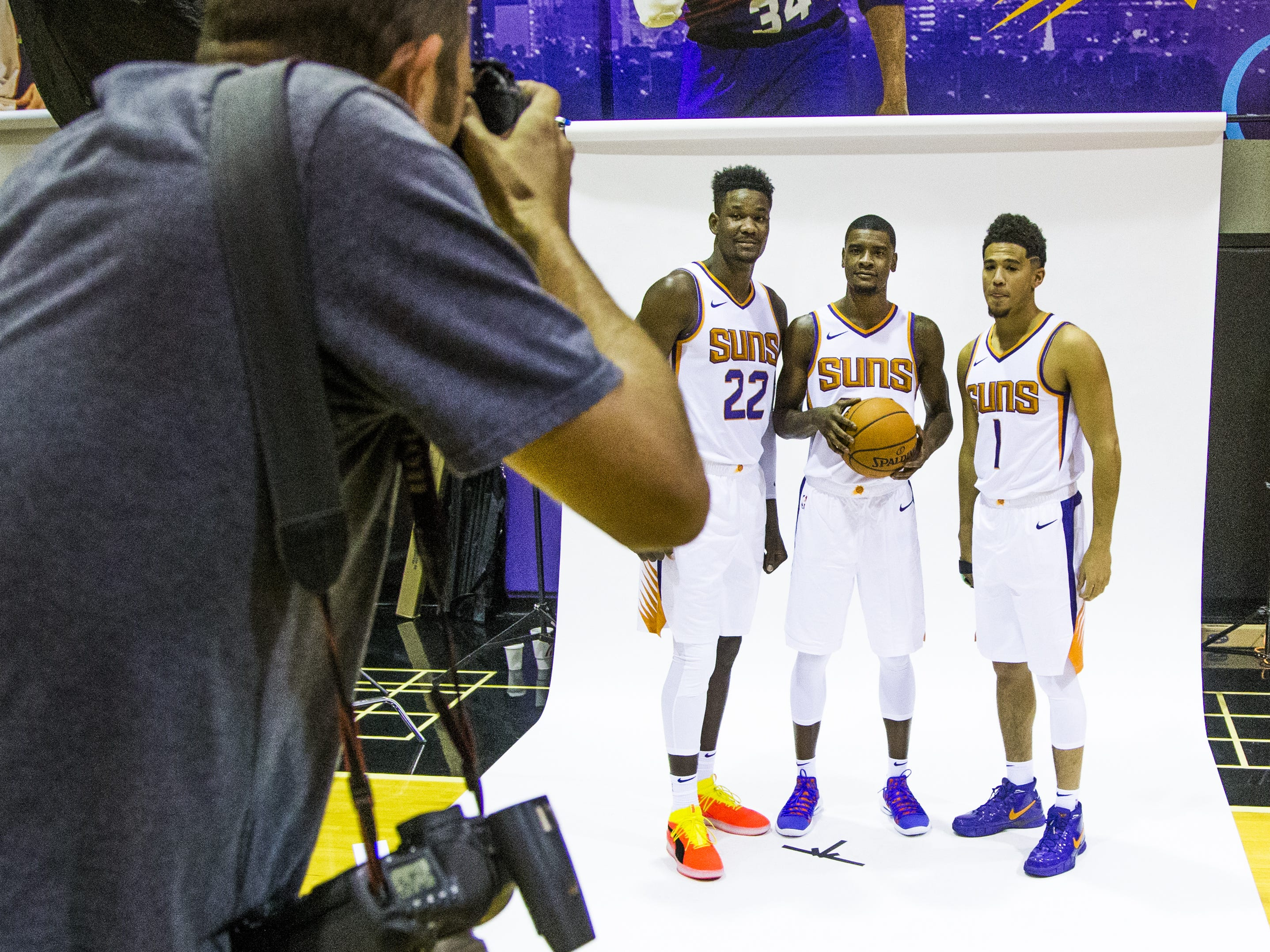 Photographer Mark Rebilas takes a photo of Deandre Ayton, center for the Phoenix Suns, forward Josh Jackson and guard Devin Booker, right, at Phoenix Suns Media Day at Talking Stick Resort Arena in Phoenix, Monday, September 24, 2018.