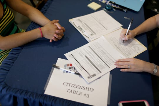 Una persona llena los formularios para solicitar la residencia de permanente residente.