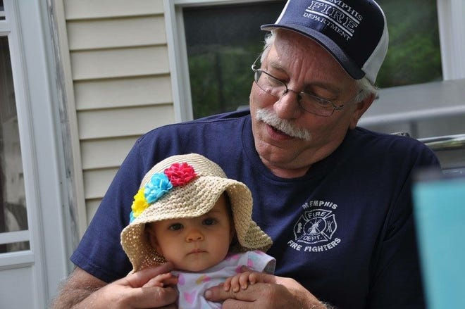 Robert Phillips II spends a moment with his granddaughter Amilia.