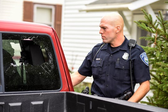 Port Huron Police Officer Nick Godwin investigates a broken window on a truck during a malicious destruction of property call Monday, Sept. 24, 2018 in Port Huron.