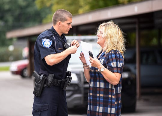 Port Huron Police Officer Jason Burge, left, goes over paperwork with Silver Pines Apartment manager Heather Reno while responding to a trespassing call at the apartments Monday, Sept. 24, 2018.