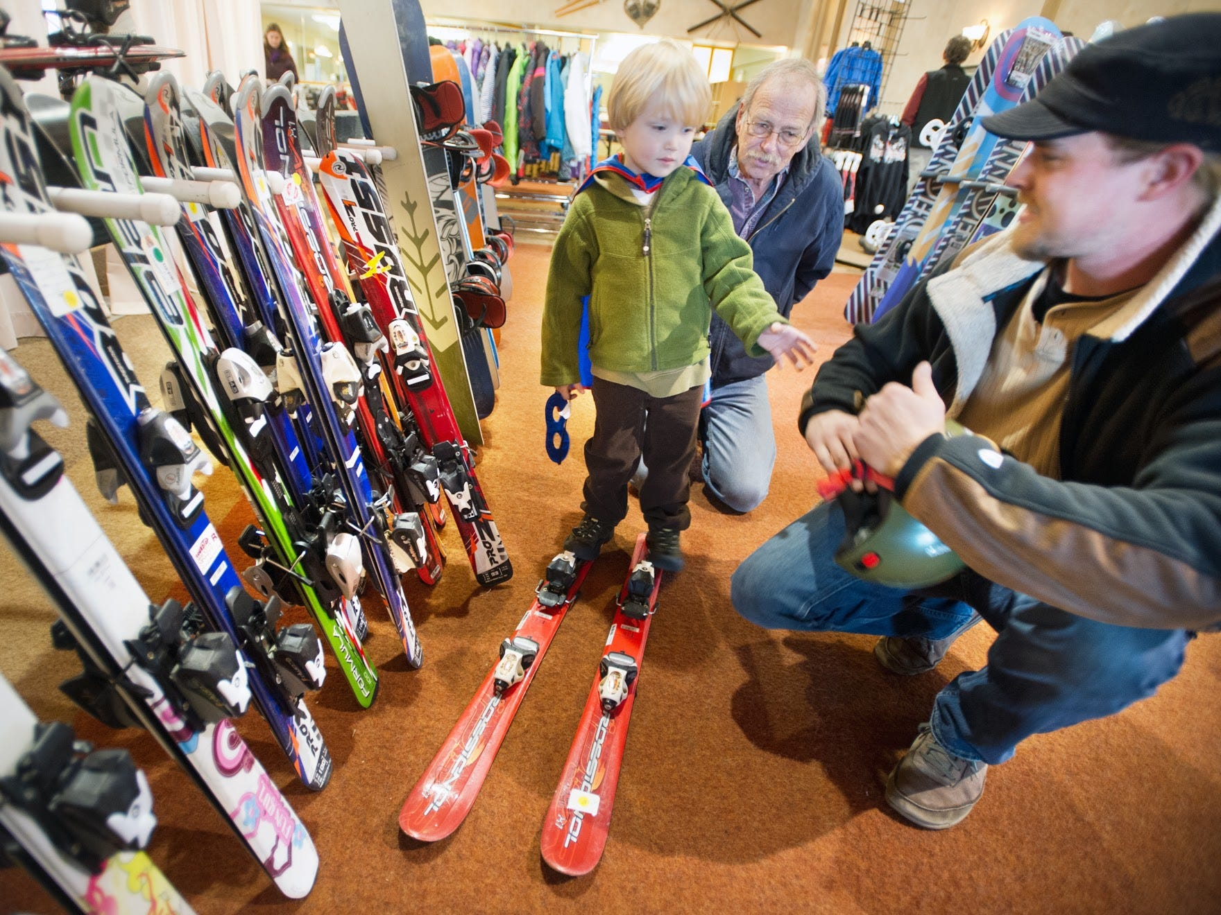 From the left, Mason Lee Miller, age 4, wears a super hero cape while trying on new skis during Roundtop Mountain Resort's Fall Extravaganza with his grandfather Jeff Miller and father Brent Miller all of Freeland Maryland on November 4, 2012