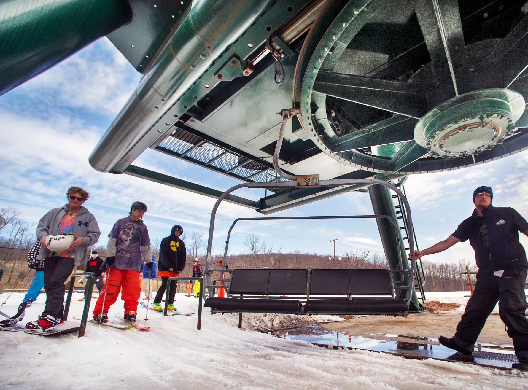 Nick Huff, a ski lift operator from Warrington Township, monitors the flow of people getting on March 11, 2014 at Roundtop Mountain Resort. Operation of the lift was back to normal Tuesday after worn-out part in what is the equivalent of a car's transmission failed in the motor room above the big pulley in the top of the frame.