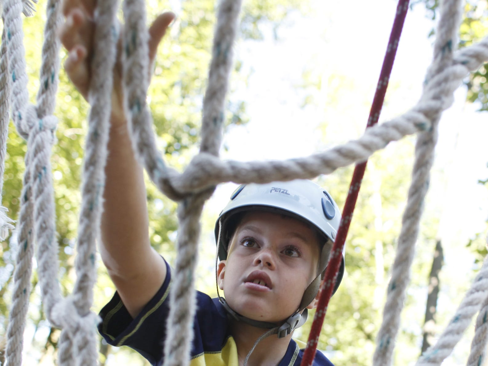 Ben Delozier, 10 of New Cumberland, climbs up the rope ladder to the zip line tower at Roundtop Mountain Resort's ropes course on Thursday, July 14, 2011.