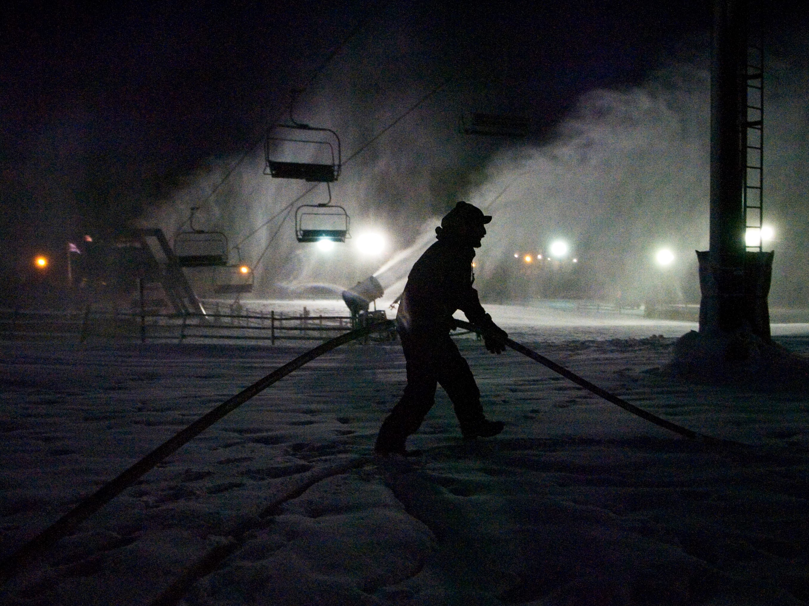 Scott Wiggins of Mechanicsburg moves a hose used to make snow at Ski Roundtop December 10, 2009.