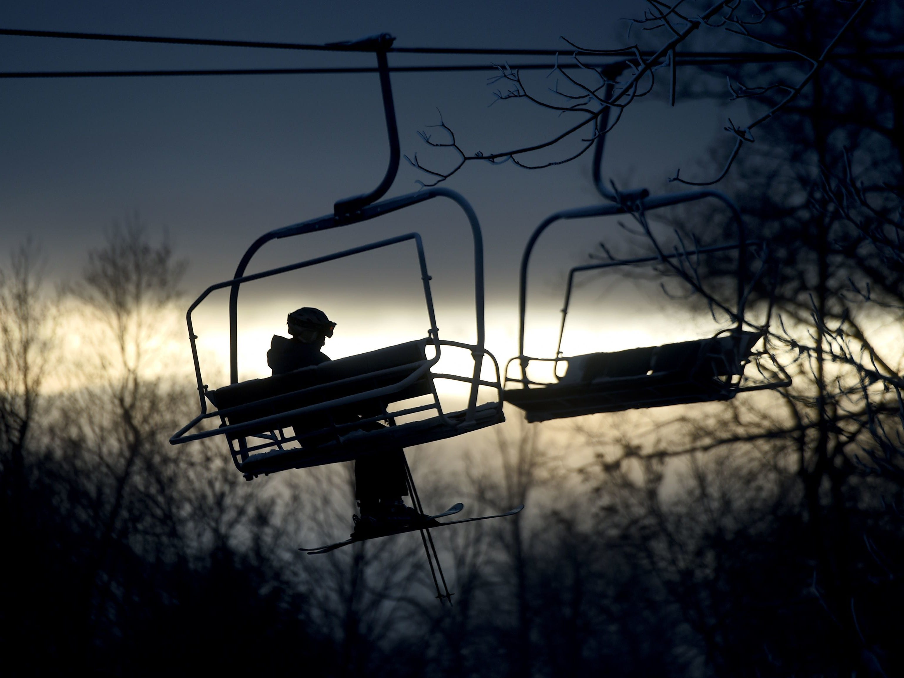 A lone skier rides a lift during the early morning at Roundtop Mountain Resort on opening day December 14, 2017.