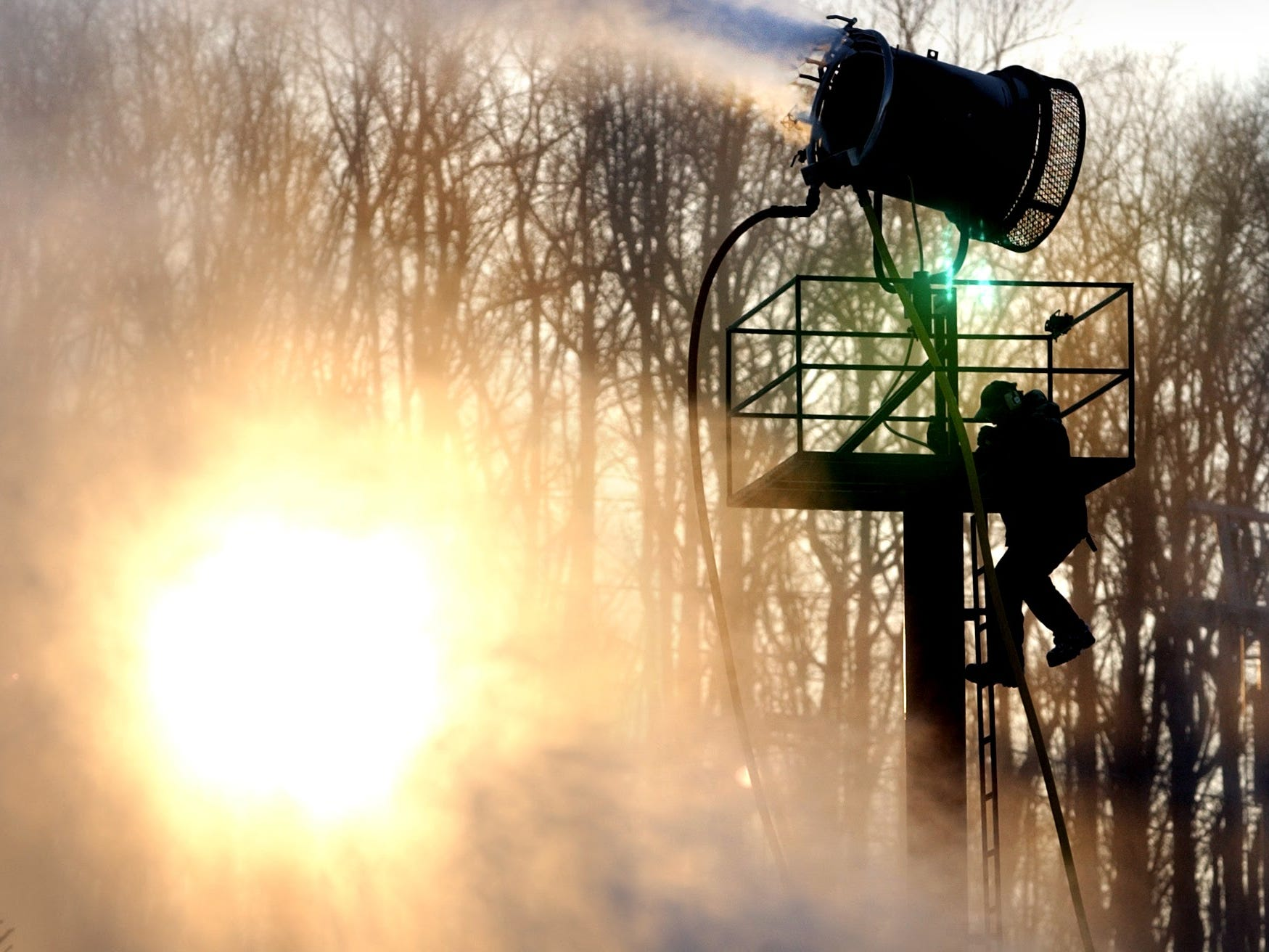Steve Wix climbs down from a snow gun at Ski Roundtop December 26, 2001. About 30-40 snow guns were running at sunset as conditions for snow making were favorable for opening day.