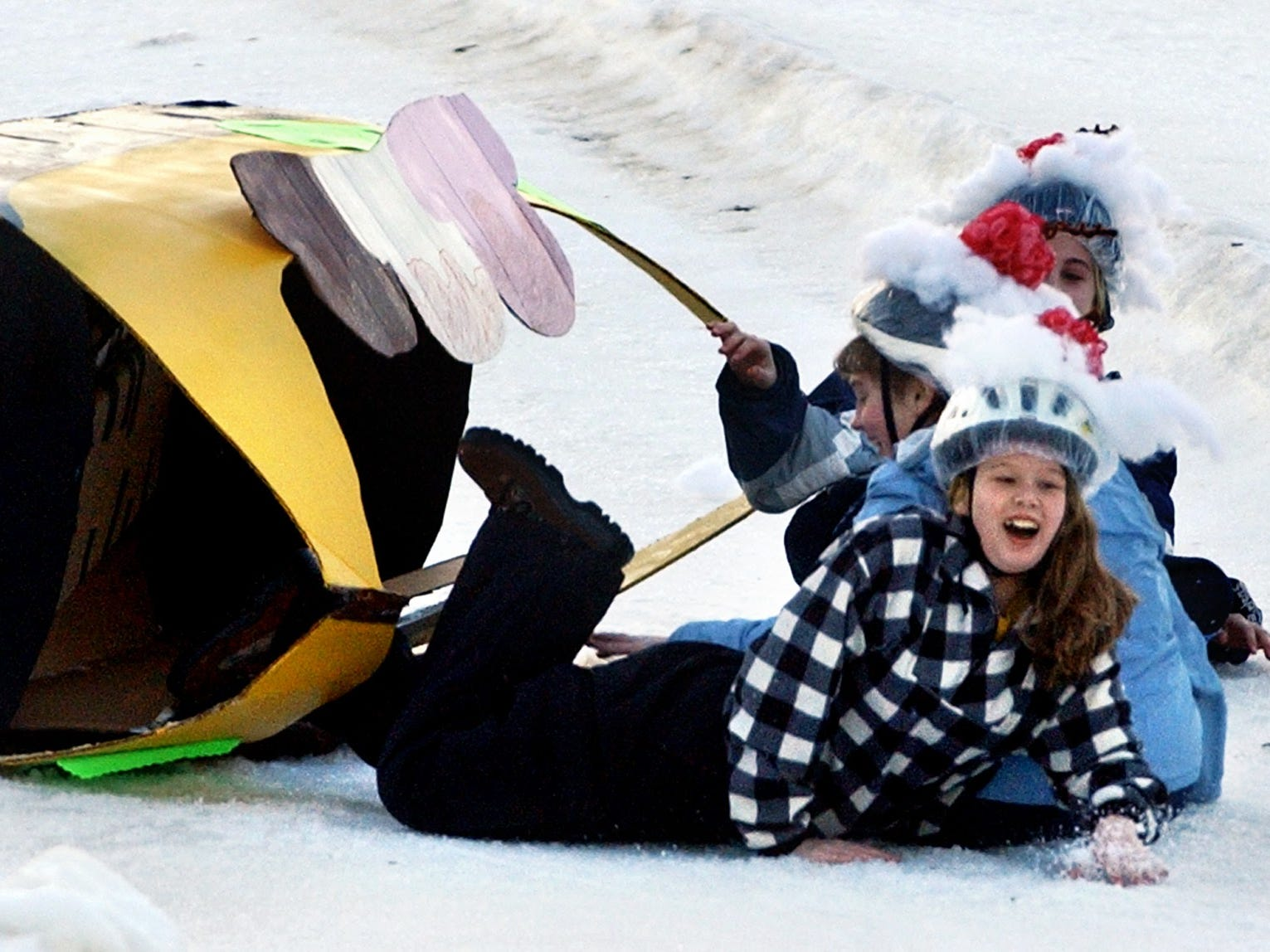 The Banana Rama takes a spill on it's way down the hill. From the front, Breanna Winters, Brandy Baltzen Krysta Myers, all of Dover, got up to make a successful second attempt during the Cardboard Snow Sled Derby at Ski Roundtop January, 27, 2002.