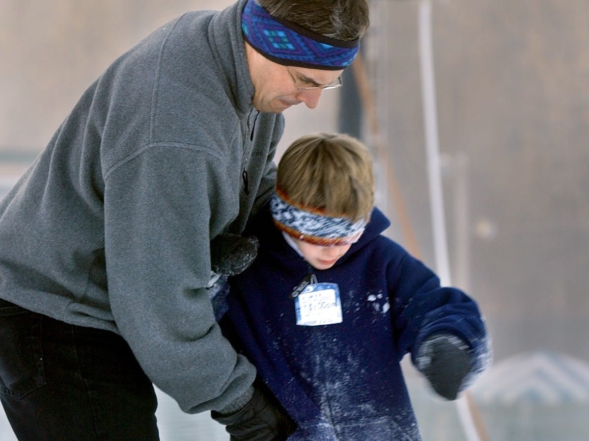 Paul Jordan, of Yorktown, Va., left, helps his son Nathan with a snowboard December 26, 2001. Nathan took snowboard lessons at Ski Rountop on opening day.