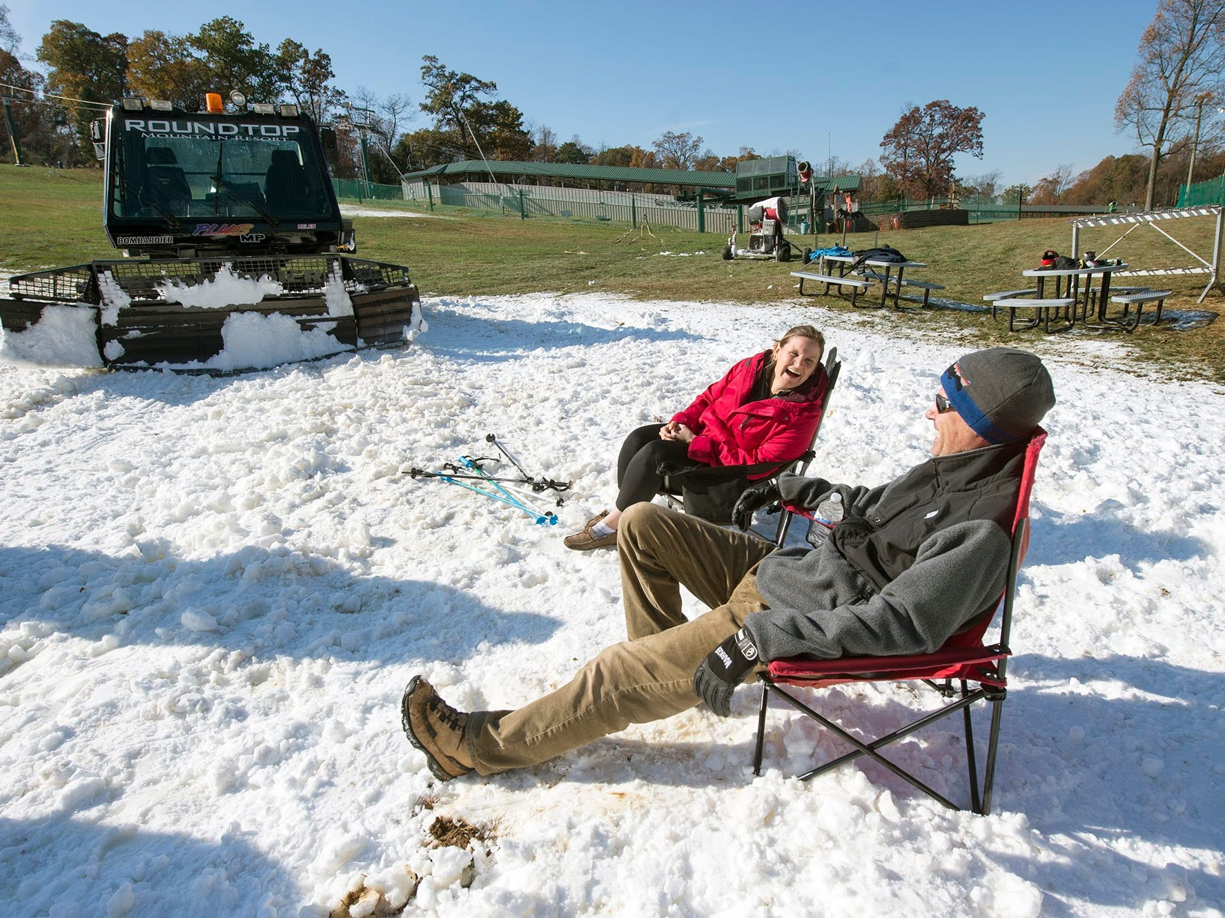 Parents Korynne McHugh, left, of Camp Hill and Jim Wheeler, of Michanicsburg, brought their lounge chairs to take in the sun while their kids skied at Roundtop Mountain Resort November 12, 2017.