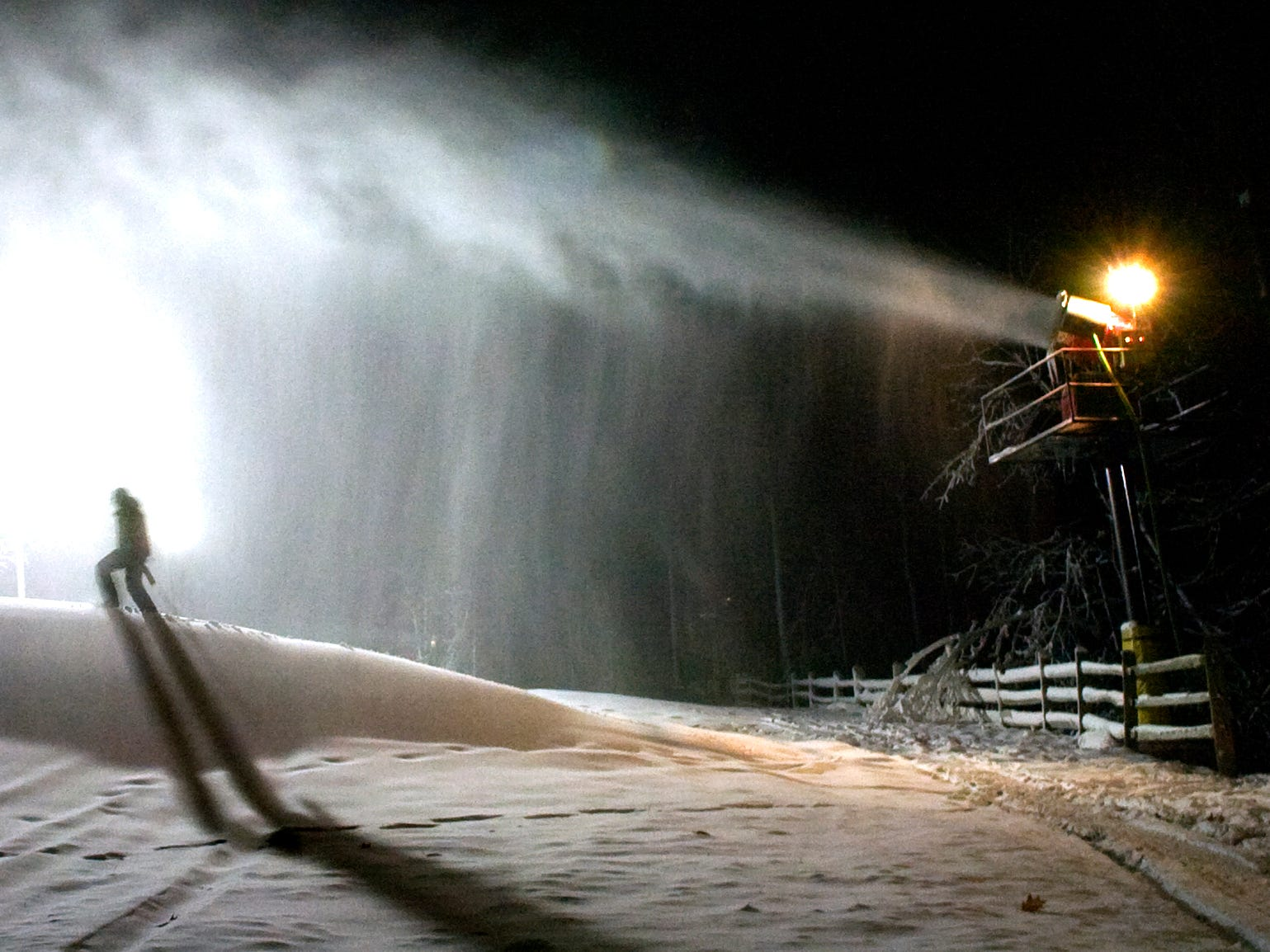 A Ski Roundtop employee walks across a hill of new snow being made before the season opening on Dec. 7, 2007.