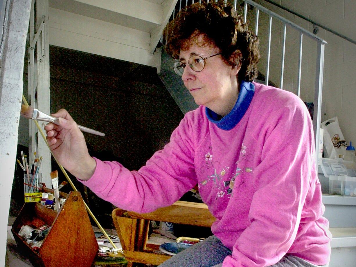 Sue Peterman paints a mural in in stairwells at Elmwood Mansion in 2000.