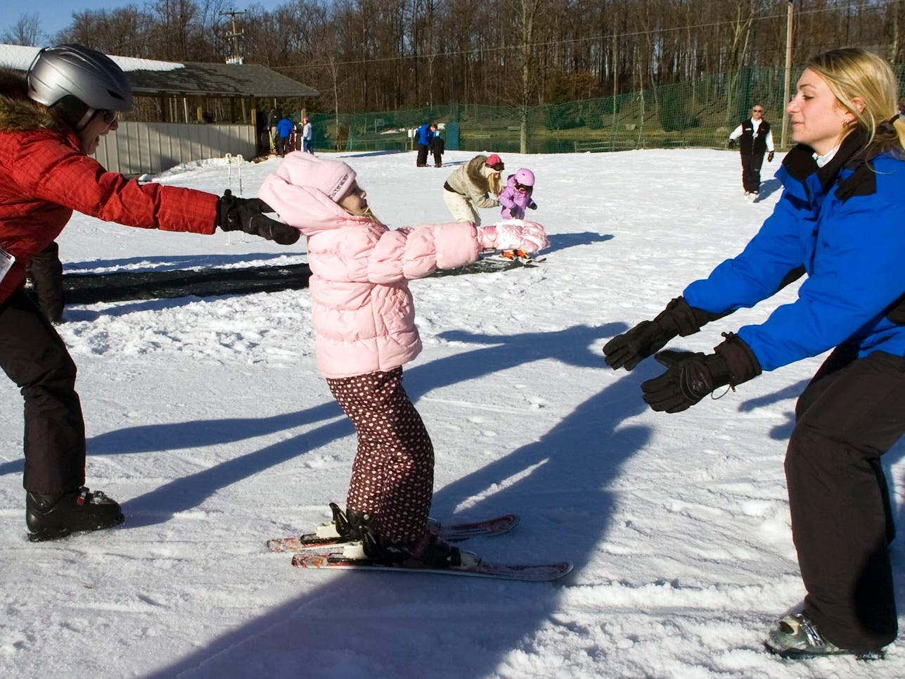 Instructors Nicole Olofson, of Mechanicsburg, left, and and Brie Hershey, of Dillsburg, spot Kylie Sharpe, age 5, of Crofton, Md. Sunday at Ski Roundtop during her first ski class December 27, 2009.