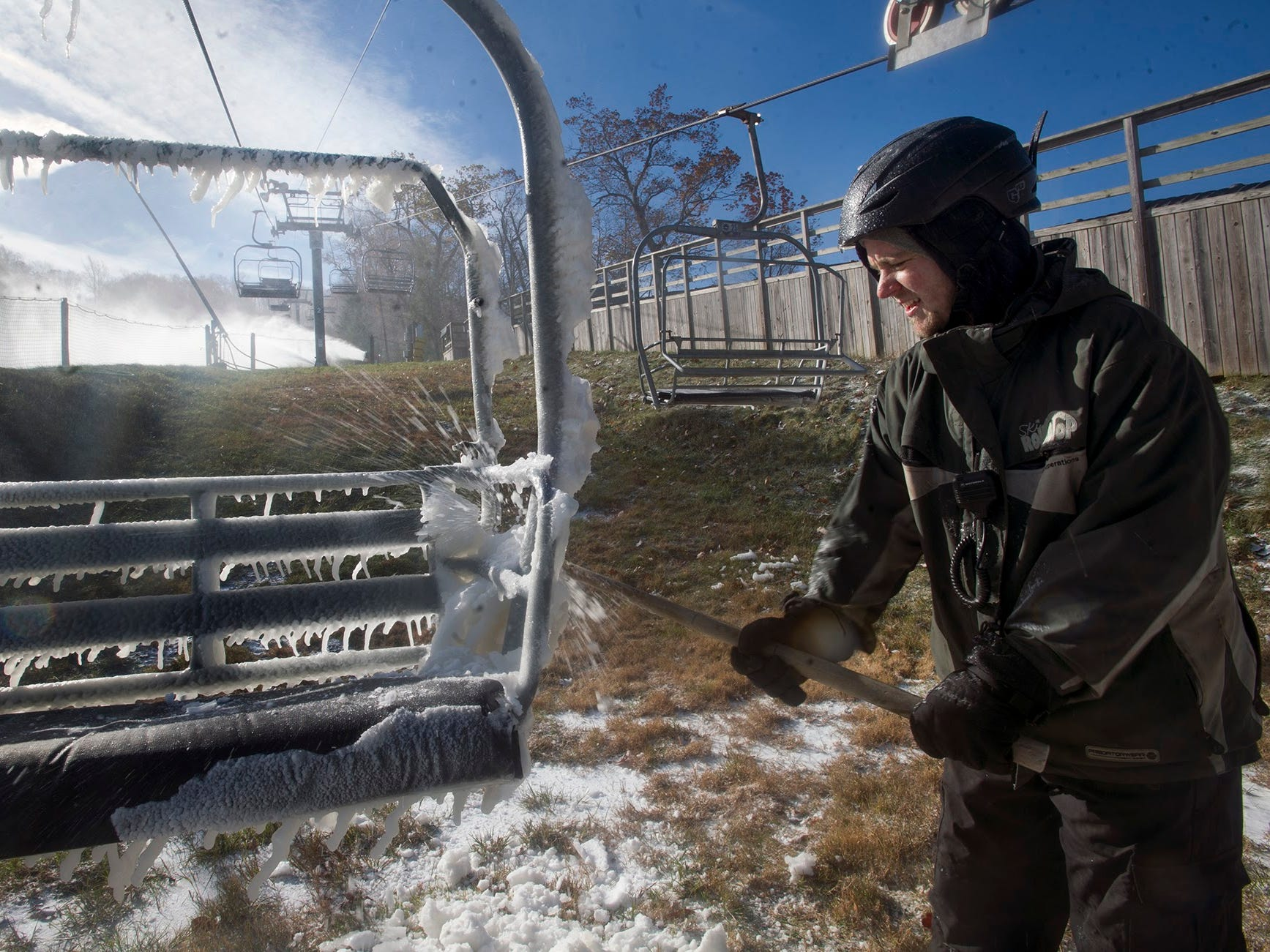 Snow maker Tommy Levendusky knocks early snow making ice off a lift chair as guns are turned on and aimed November 18, 2014.