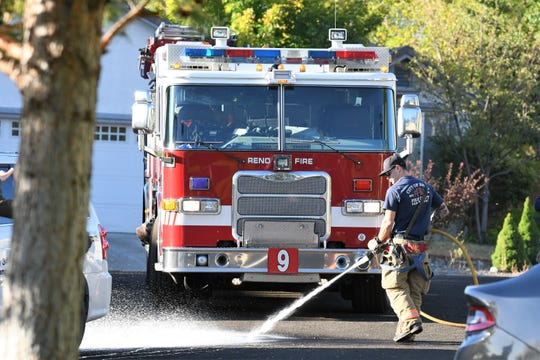 The Reno Fire Department cleans up fluids that leaked from a vehicle with multiple bullet holes in the windshield and engine compartment after a man was shot by the Reno Police Department on Sunday, Sept. 23.