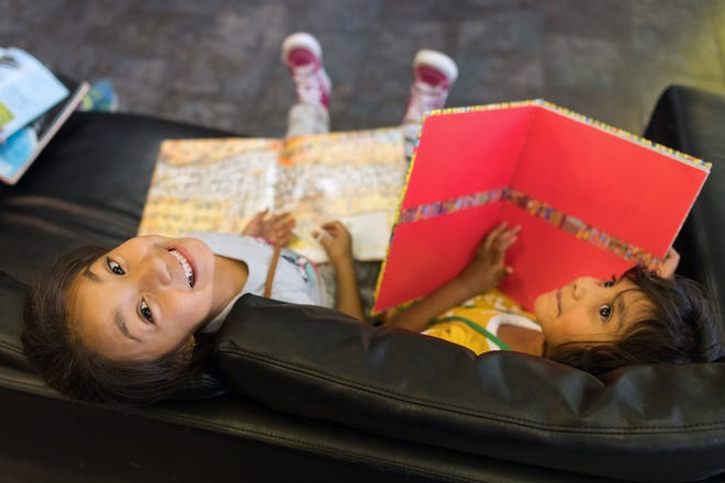 Genesis Fragoso, 6, (left) and Daryna Castillo, 6, take a break from reading.