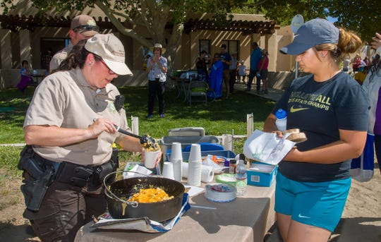 Jennifer Dawson, from Nevada State Parks, left, dishes up a cup of her Dutch oven Nevada casserole to a visitor.