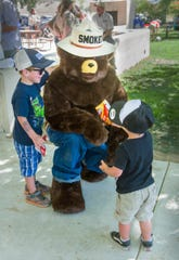 Colton Shasha, 2, of South Lake Tahoe, right, offers Smoky Bear some chips as his brother Walker, 4, watches.