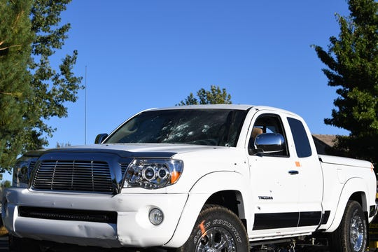 A white pickup truck with multiple bullet holes in the windshield, engine compartment and door being taken away from the scene where a man was shot by the Reno Police Department on Sunday, Sept. 23.