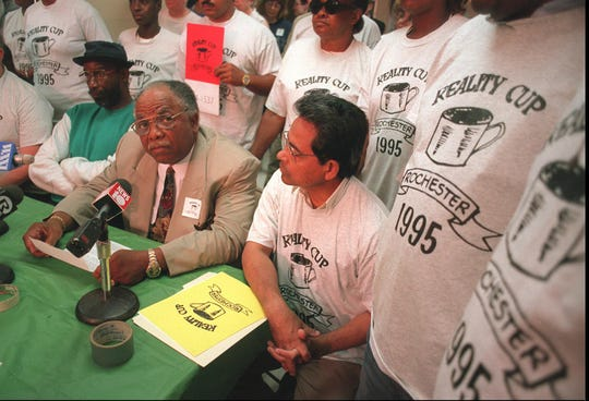 """The Rev. Franklin Florence, left in tan suit, makes a statement to the media July 12, 1995, about the Ryder Cup and how all the media hype about the event is overshadowing the city's real problems. Supporters wore T-shirts with a logo for the """"Reality Cup."""""""