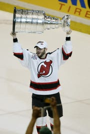Greece native Brian Gionta of the New Jersey Devils hoists the Stanley Cup after defeating the Mighty Ducks of Anaheim in game seven of the 2003 Stanley Cup Finals at Continental Airlines Arena on June 9, 2003 in East Rutherford, New Jersey. The Devils defeated the Ducks 3-0 to win the Stanley Cup.