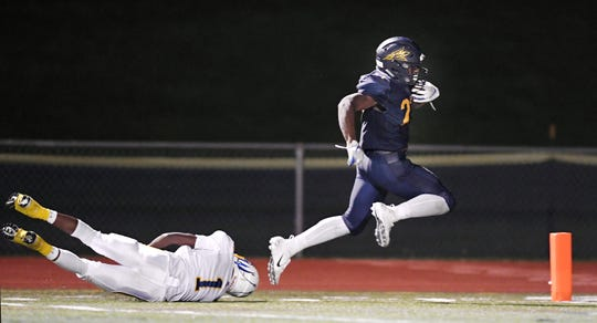 Victor's Rushawn Baker, right, breaks a tackle by Irondequoit's JaRon Frith to score the Blue Devils'  third touchdown and tie the score 21-21 during a regular season game played at Victor High School, Sunday, Sept. 23, 2018. Irondequoit beat Victor 28-21.